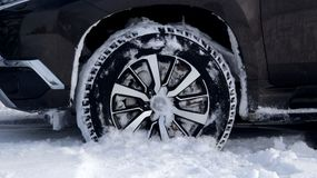 Winter tires on the off road truck wheel in the deep snow close up stock photo. Wheel of SUV vehicle with winter all-terrain tire in the deep snow with tread Royalty Free Stock Photo