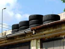 winter tires stored on top of decaying garage roof stock image