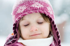Winter toddler girl in pink hat. Toddler girl in warm pink hat under snowflakes stock photos