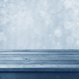Winter toned bokeh background. With wooden table royalty free stock photography