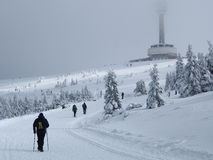Winter tourism. Tourists in the winter going up the hill Royalty Free Stock Images