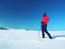 Winter tourist with snowshoes walk in snowy drift. Hiker in pink sports jacket Stock Images