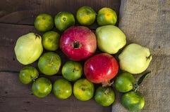 Winter trägt auf Bretterboden, Quitte, Granatapfel, Mandarinenbilder Früchte Stockfotografie