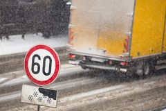 Winter traffic jam during snowstorm with poor visibility. Speed limit sign with a traffic jam in the background on a slippery high. Winter traffic jam during Royalty Free Stock Photography