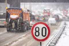 Winter traffic jam during snowstorm with poor visibility. Speed limit sign with a traffic jam in the background on a slippery high. Winter traffic jam during Stock Photos