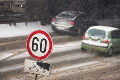 Winter traffic jam during snowstorm with poor visibility. Speed limit sign with a traffic jam in the background on a slippery high. Winter traffic jam during Stock Images