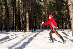 Winter trail running: man takes a run on a snowy mountain path in a pine woods. Stock Photography