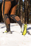 Winter trail running: man takes a run on a snowy mountain path in a pine woods. Royalty Free Stock Photography