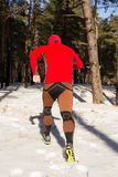 Winter trail running: man takes a run on a snowy mountain path in a pine woods. Royalty Free Stock Photo