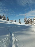 Winter trail on the snow. Winter scene  on the mountain with some thin clouds against blue sky Royalty Free Stock Images