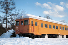Winter train. Bright orange train inmidst a sunny winter landscape on Hokkaido, Japan Stock Photo
