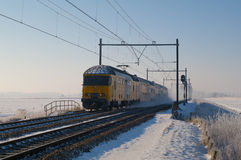 Winter train. Yellow train speeding through a snowy winter landscape. Freezing conditions often causes delays for public transport and commuters Stock Images