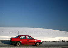 Winter Travel. A red car traveling on a road surrounded by snow covered wintry landscape royalty free stock photography