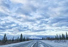Winter Travel on Alaska Highways. Winter travel in Alaska is full of many dangerous situations.  Snow on the roadway as well as icy patches, makes for tough Royalty Free Stock Photo