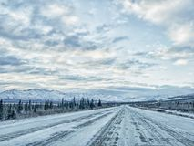 Winter Travel on Alaska Highways. Winter travel in Alaska is full of many dangerous situations.  Snow on the roadway as well as icy patches, makes for tough Stock Photo