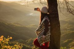 Winter Travel. Asian woman wearing coat standing by the mountain,Cold weather,fog on hills,Winter hiking,Travel in Chiang Mai,Thailand Stock Image