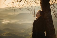 Winter Travel. Asian woman wearing coat standing by the mountain,Cold weather,fog on hills,Winter hiking,Travel in Chiang Mai,Thailand Royalty Free Stock Photos