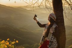 Winter Travel. Asian woman wearing coat standing by the mountain,Cold weather,fog on hills,Winter hiking,Travel in Chiang Mai,Thailand Royalty Free Stock Image