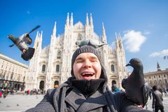 Winter travel, vacations and birds concept - Young funny man taking selfie with pigeons near Milan Cathedral Duomo di. Milano, Italy royalty free stock image