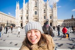 Winter travel, vacations and birds concept - Young happy woman tourist with funny pigeons making selfie photo in front stock photo