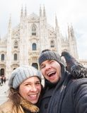 Winter travel and vacations concept - Happy tourists taking a self portrait with funny pigeons in front of Duomo. Cathedral in Milan royalty free stock photography