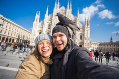 Winter travel and vacations concept - Happy tourists taking a self portrait with funny pigeons in front of Duomo. Cathedral in Milan royalty free stock images