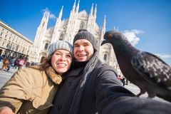 Winter travel and vacations concept - Happy tourists taking a self portrait with funny pigeons in front of Duomo. Cathedral in Milan royalty free stock image