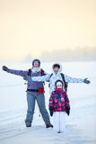 Winter travelers stand on ice of frozen lake in warm clothes and smiling Royalty Free Stock Photo
