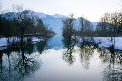 Winter trees with reflection in a lake, mountains in the backgro Stock Images
