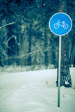 Winter trees with road sign. Picture of winter day with trees with road sign of bicycle path in frost. Toned photo Royalty Free Stock Image