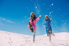 Winter, twee meisjes die pret in de sneeuw in de bergen de hebben Stock Fotografie