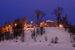 Winter twilight. In a small town standing on abrupt river bank Stock Photo