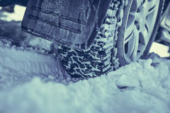 Winter tyre  on a  snowy road. Closeup of winter tyre  on a  snowy road Royalty Free Stock Photo
