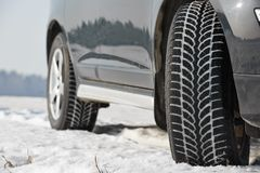 Winter tyres wheels installed on suv car outdoors. Car with winter tyres installed on light alloy wheels in snowy outdoors road stock photos