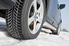 Winter tyres wheels installed on suv car outdoors. Car with winter tyres installed on light alloy wheels in snowy outdoors road stock photography