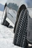 Winter tyres wheels installed on suv car outdoors. Car with winter tyres installed on light alloy wheels in snowy outdoors road Stock Image