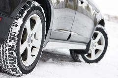 Winter tyres wheels installed on suv car outdoors. Safety driving. Car with winter tyres installed on light alloy wheels in snowy outdoors road Stock Image