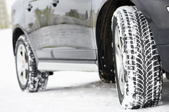Winter tyres wheels installed on suv car outdoors. Safety driving. Car with winter tyres installed on light alloy wheels in snowy outdoors road Royalty Free Stock Images