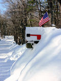 Winter: US mail box in snow. White mail box with US flag half buried in snow Stock Photo