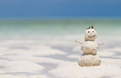 Winter vacation. Snowman made from white tropical sand on exotic beach with ocean on background Stock Photo