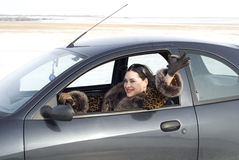 Winter vacation. Happy woman sitting in the car Royalty Free Stock Image