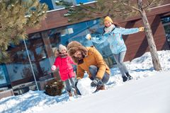 Winter vacation. Family time together outdoors mother and daughter running to hit father with snowballs laughing excited stock image