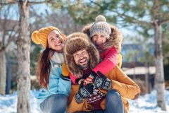 Winter vacation. Family time together outdoors sitting hugging laughing cheerful close-up blurred background royalty free stock photography
