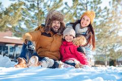 Winter vacation. Family time together outdoors sitting hugging smiling happy close-up stock photography