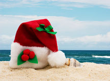 Winter vacation getaway. A Christmas hat the sand at the beach, Winter vacation getaway Stock Images