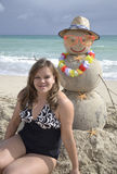 Winter vacation. Portrait of the woman at the beach on winter vacation with snowman made out of sand Royalty Free Stock Images