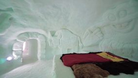 Winter vacation at the ski resort. Stunning interior in icy room at ice hotel. Frozen room made of ice and snow at