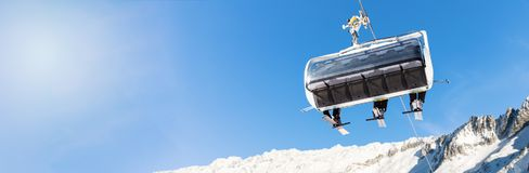winter vacation - skiers in a chairlift against blue sky Stock Photos