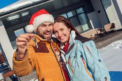 Winter vacation. Young couple standing together outdoors with keys from new apartment smiling excited close-up stock images
