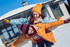 Winter vacation. Young couple standing together outdoors near house making flying pose laughing playful stock photo